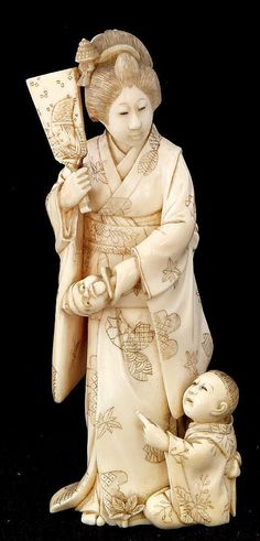 A Japanese carved and stained okimono Meiji period (1868-1912), modelled as an actress and a young boy, the young female figure holding a mask in one hand a paddle in the other, whilst a small boy sits at her feet, signed, 14cm high