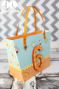 "I had such a good time making things for my nephew's 6th birthday, like this Shark Frisbee and ice cream cone box and star card, that I decided I needed to put everything in a sweet bag too!  I used the ""Beach Tote"" from the Luxury Handbags file by SVGCuts to create this kid friendly bag. I …"