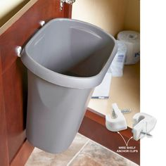 Screw wire shelf anchor clips to the inside of the door and hook the lip of a small wastebasket right on the hooks.