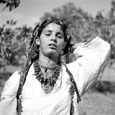- Besancenot Jean (1902-1992) Femme berbère Ouled Yahia. Son cou et son visage sont tatoués. Elle porte un collier fait de pièces d'argent enfilées de profil.- Arago