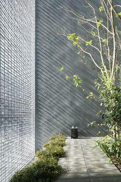 glass block wall facade enclosing courtyard . Optical Glass House . Hiroshi Nakamura & NAP Co . Hitroshima, Japan