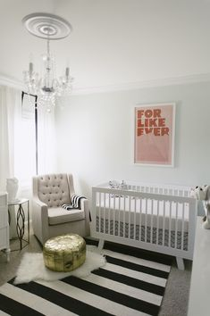 Pale mint nursery with black and white striped rug, chandelier, golf pouf