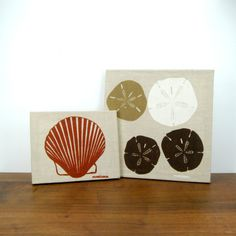 This set of two (2) vintage wall hangings are a canvas or linen material over a pine wood frame with a scallop shell and sand dollars printed on