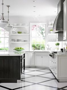 Amazing kitchen features a pair of schoolhouse pendants illuminating a black island topped with contrasting white marble.