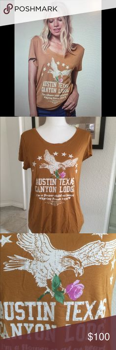 """SPELL & The GYPSY COLLECTIVE """"Austin"""" Tee!✨ BRAND NEW WITH TAGS!  Super Cool Austin Tee in M. This Gorgeous Texas Tee comes in new 100% Viscose fabric which feels just as soft as Cotton, you'd swear it is. The fabric is super light and floaty with a relaxed fit. In a """"Mustard"""" colour, which to me looks like a light Vicuna Brown. The front logo is vintage-inspired artwork and that Pop of Pink is bright! This colour looks Gorgeous on blondes! I wasn't sure if it would look good on a Brunette…"""