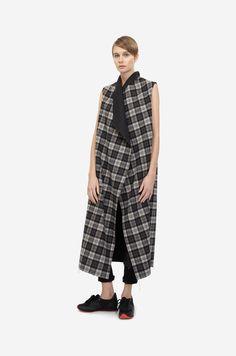 LONG PLAID VEST Shorthaired model wearing a black & grey checkered wool vest with black sneakers. Design: Lucie Kutálková / LEEDA