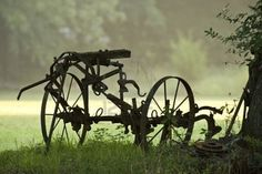 Rusted farm equipment silhouetted in the morning fog.