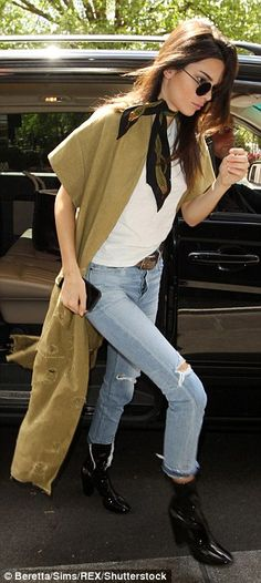 Kim Kardashian displays her ample cleavage in a curve-hugging dress