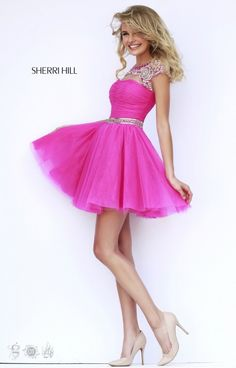 Ladies! Take it from us, it doesn't get much cuter than Sherri Hill 11191! This sassy and spunky short dress has it all! The top features a scoop neckline and cap sleeve with a cleavage cut out over a slight modest sweetheart top. The top is embellished in the most detailed and delicate design of rhinestones, sequins and gems over sheer mesh. The back includes the same jaw dropping design of embellishments with a clasp at the top, and a key hole cut out. The bodice includes a ruched design…