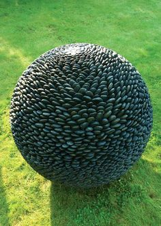 Dark Planet Garden Sphere by David Harber ....takes a bowling ball, adhesive, rocks, and time to make your own.
