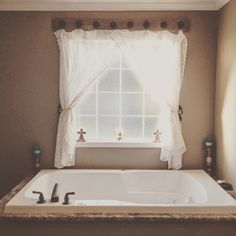 Bathroom window project: found a weathered board, drilled holes, insert cast iron door handles from hobby lobby. Vintage curtains from eBay. Clipped curtain hoops bought from hobby lobby. Curtain tie backs I made knotted loops with burlap rope and hung on glass doorknob on cast iron plate with keyhole. Total project $45