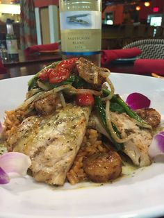Mesquite WoodGrilled, North Carolina Rainbow Trout.  About the dish: NC Rainbow Trout, mesquite wood grilled with blackened shrimp, sautéed bean sprouts, scallions, dirty island red rice and tomatillo sauce.  Marley's Island Grille, Hilton Head, South Carolina.