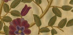 Purna Crewel Fabric A fine hand crafted floral crewel in aubergine and green on a sand yellow cotton.