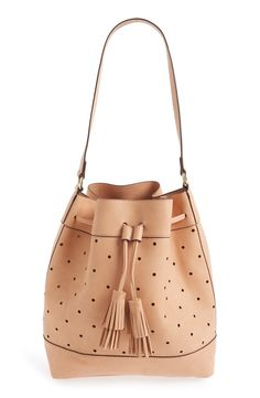 Buttery-soft faux leather and a lightly structured silhouette make this perforated bucket bag a chic everyday choice. A pair of swingy tassels gives it a bohemian touch, while a roomy interior easily accommodates all of the necessities.
