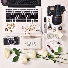 flat lay fashion: celine me alone clutch, mac laptop, white roses, gold jewellery, camera