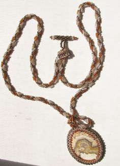Cabachon bezel pendant with spiral seed bead necklace in shades of gold, bronze, pale blue.  $40.00.  jadeawd@yahoo.com
