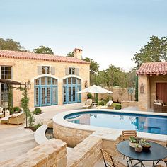 Courtyard | The elevated swimming pool's shape recalls an old ranch cistern. | SouthernLiving.com | Architect: Michael G. Imber Architects and Interior Design: Mohon-Imber Interiors | #SLIdeaHouse