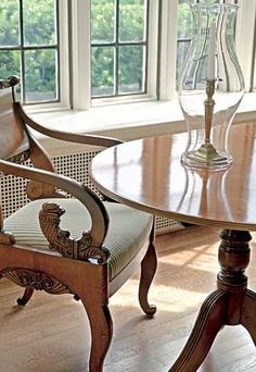 A period Sheraton table and an antique French chair sit in this dining room alcove - Traditional Home®