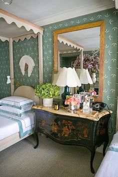 A very layered & eclectic mix helped by color -- the green trim of the bedding ties in with the wallpaper.