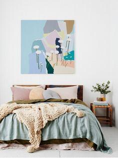 Cette chambre aux murs blancs joue sur des touches de couleurs grâce à un tableau et au linge de lit
