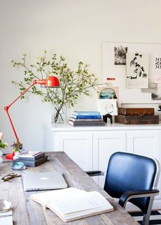 Bright office space with a reclaimed wood desk, retro chair and a orange task lamp