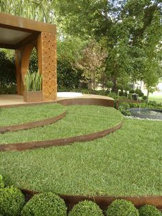 Sinuous curves of cor-ten steel edged lawn sweep across Paal Grant's 'Conversation' garden
