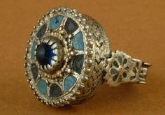 Сребрни прстен. Око средишњег рама у коме се налази плави камен распоређена су поља испуњена наизменично плавим и црним емајлом. Припада типу столоватог прстења. Etnografski muzej Beograd