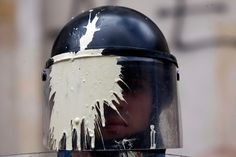 A riot police officer with his mask stained with paint thrown by students watches a march by teachers and students protesting a wide range of issues regarding the governments educational policies in Bogota, Colombia, on Sept 5.