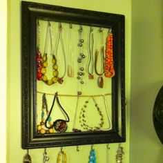 Love to see all of my necklaces on this! I wear them so much more!  Garage sale backless frame. Drilled cup hooks at regular intervals on top and bottom. Then used the hooks for the wire mounting to hang the string. I also added some claw hooks to the back to hang it on a wall.
