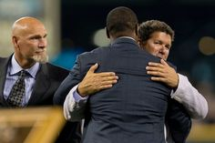 Ken Griffey Jr., center, hugs Edgar Martinez while fellow former teammate Jay Buhner looks on.