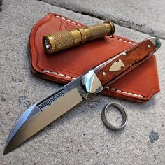 Pocket dump picture with Northwoods Fremont Jack slipjoint knife in brown giraffe bone, Maratac AAA brass flashlight