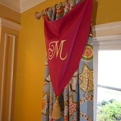 Love the triangle monogrammed swag over coordinating drape! Could work in any room! (Elephant Walk Curtain Panel from PoshTots