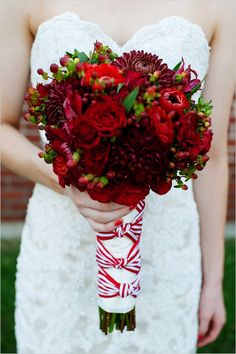 Red dahlias, red hypericum berries, anemones and roses!  Love the bouquet.  Not sure about the ribbon.