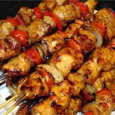 Honey Chicken Kabobs  1/4 cup vegetable oil  1/3 cup honey  1/3 cup soy sauce  1/4 teaspoon ground black pepper  8 skinless, boneless chicken breast halves - cut into 1 inch cubes  2 cloves garlic  5 small onions, cut into 2 inch pieces  2 red bell peppers,