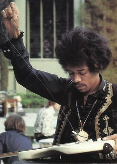 "Jimi restringing his own guitar - roadie ""H"" can be seen in the background"