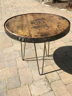 This is a one of a kind bourbon barrel top table. Made out of a genuine Kentucky bourbon barrel top, with an attached barrel ring around the top, or without a ring attached. The top sets on 3, made in the USA, hairpin style legs . The table top is about 22 in diameter and sets about