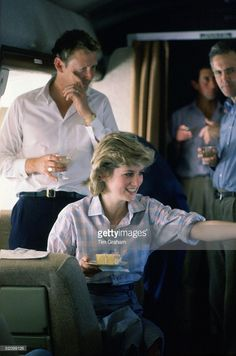Prince Charles And Princess Diana On Board A Royal Australian Air Force Plane Refuelling In Fiji Before Continuing To Australia. With Their Staff Commander Brian Robertson (the Australian Equerry To Prince Charles For The Royal Tour) And Sir John Riddell (the Prince's Private Secretary) They Are Holding An Impromptu Birthday Celebration For The Valet