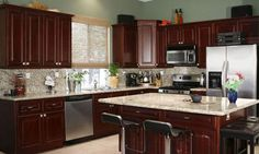 Dark Cherry cabinets with light countertops and back splash. Wood floors instead of tile. Kitchen color paint