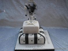 Black white and silver themed two tier stacked parcel birthday cake. Decorated with silver and black stars and topped with a feather and star wired topper including glittered number 50. Finished with silver glitter ribbon rope
