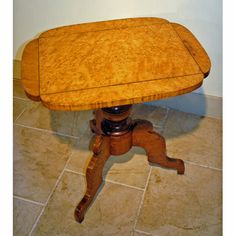 Folksy tilt-top table in outstanding Bird's-eye Maple with scroll base, late 19th century.