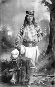 """Studio portrait of Ba-keitz-ogie (Yellow Coyote), U. Army Scout a Native American (Chiricahua Apache) man. He holds a rifle and wears moccasin boots, a breechcloth, ammunition belt, and a kerchief on his head. Title and """"one of the most notorious. Apache Native American, Native American Images, Native American History, American Indians, American Symbols, Les Scouts, Western Comics, Geronimo, Native Indian"""