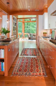 Galley kitchen that opens into a huge sunroom....love the surrounding forest
