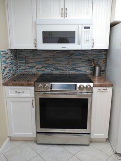 Le joint mur comptoir s'est réalisé avec des carreaux plus étroits et dans les tons du comptoir. Voilà, la cuisinière se cale bien contre le mur du fond.  Celui-ci est protégé des projections de cuisine par un carrelage qui apporte de la lumière et une touche de couleur. Mission réussie !