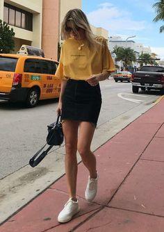 10 looks para quem ama praticidade. T-shirt amarela, minissaia preta, tênis branco
