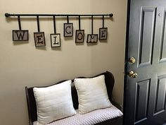 DIY Entryway Welcome Sign replace rod with wood and ribbon with barbed wire, using old barn wood or pallet pieces for the letters