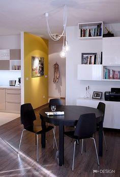 Mieszkanie w Katowicach (2 pokoje, 64 m kw.) - salon; proj. M+Design. Jasne ściany oraz proste, białe meble stanowią tło dla pojawiających się gdzieniegdzie czerni i szarości.