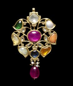 A gem-set Navaratna gold Pendant, India, 20th Century, in the form of a flowerhead, set in an open gold framework with a diamond, mother of pearl, coral, hessonite, blue sapphire, cat's eye chrysoberyl, yellow sapphire and emerald, with smaller diamonds set in gold tendrils surrounding a central ruby, a ruby bead with three seed pearls suspended below, gold suspension loop above, the reverse with repousse floral decoration, 7.3 cm. long; 23 g.