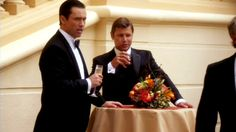"""[voice-over] """"It's a cliché that spies wear tuxedos in the field. While there's some truth to it, you don't usually wear them to baccarat tables in Monte Carlo. Most of the time you're in black tie it's at rubber chicken dinners, political fund raisers or charity auctions. Not quite as glamorous as the French Riviera but at least you'll usually get free drinks."""" [Michael Westen]   Pictured: Michael Westen (Jeffrey Donovan) and Max (Grant Show)"""