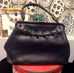 Navy Blue pebbled leather handbag circa 1960. Has a doctor bag look. Large lacing on front 13 inches at the widest point. 9.5 inches at the