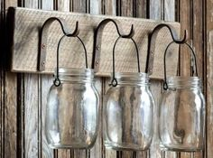 "Metal hooks mounted on distressed board hold three hanging canning jars. 18"" x 4"" x 12"""